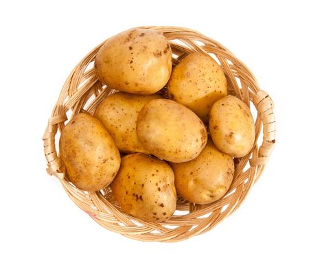 Potatoes in a wicker basket isolated on white background photo
