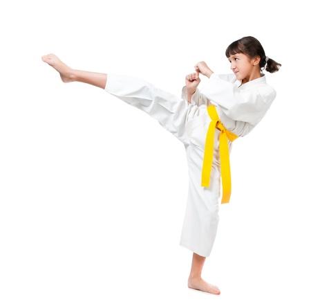kick: bambina in un kimono con una fascia gialla su sfondo bianco Archivio Fotografico