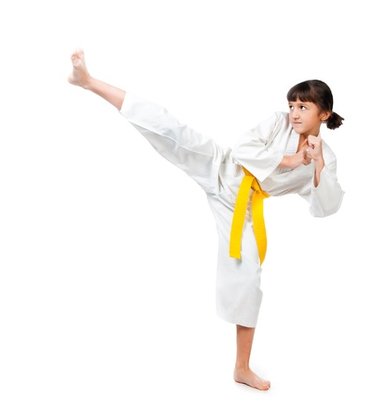 karate fighter: little girl in a kimono with a yellow sash on a white background Stock Photo