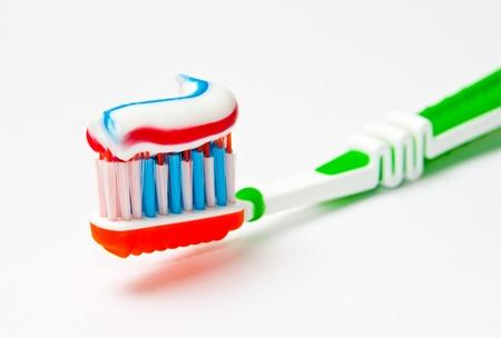 pasta dental: cepillo de dientes con pasta dental con tres colores sobre fondo claro
