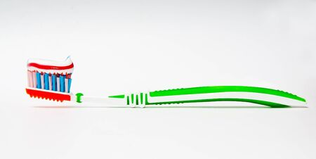 toothbrush with tricolor toothpaste  on light background photo