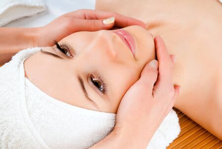 beautiful young woman lying relaxed in a spa salon and receiving facial massage photo