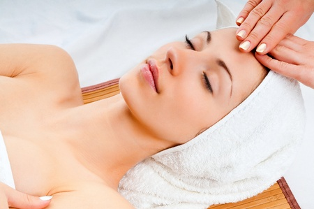 facial treatment: Beautiful young woman receiving facial massage with closed eyes in a spa center