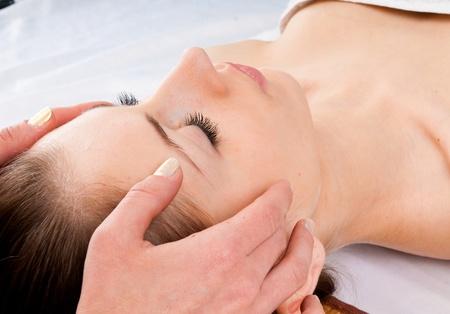 tratamiento facial: Joven y bella mujer recibiendo masaje facial con los ojos cerrados en un centro de spa