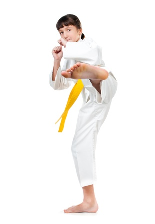 jujitsu: little girl in a kimono with a yellow sash on a white background Stock Photo