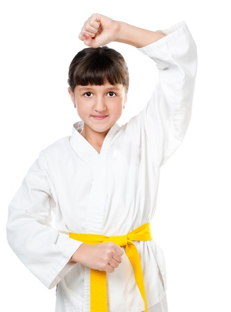 girl punch: little girl in a kimono with a yellow sash on a white background Stock Photo