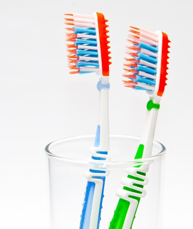 toilet brush: two toothbrushes in a glass beaker on a light background Stock Photo