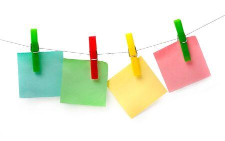 attach: tres piezas de papel de color para las notas colgando de ganchos