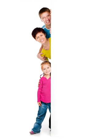 family and health: Beautiful fun family behind a white blank Stock Photo