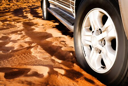 wheel of a car on the sand in the desert photo