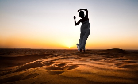 young woman in sandy desert at sunset photo