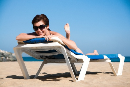 pareo: beautiful girl relaxes on a lounger in sunglasses