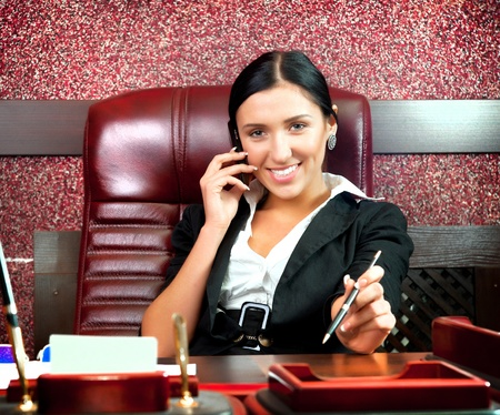 active young businesswoman in an office with telephone photo