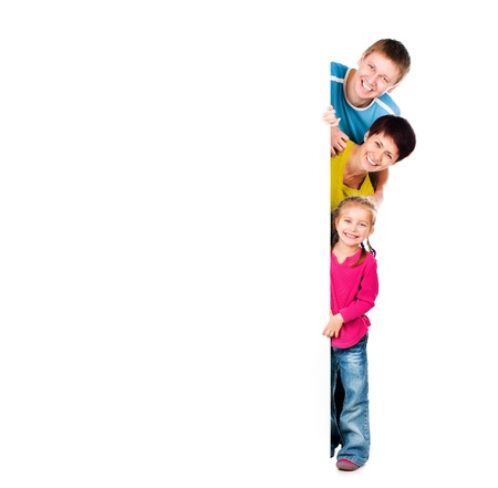 family health: Beautiful fun family behind a white blank Stock Photo