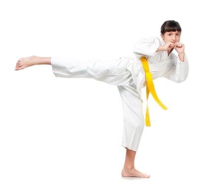 karate female: little girl in a kimono with a yellow sash on a white background Stock Photo