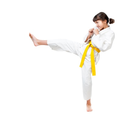 girl kick: little girl in a kimono with a yellow sash on a white background Stock Photo