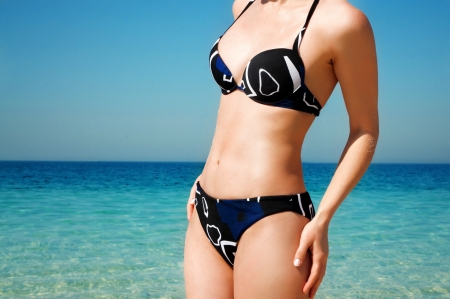 corfu: torso of a girl in a bathing suit against the sea Stock Photo