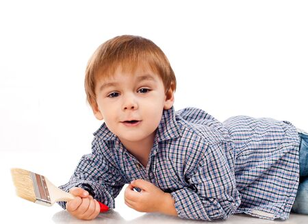 little boy with paintbrush on a light background photo