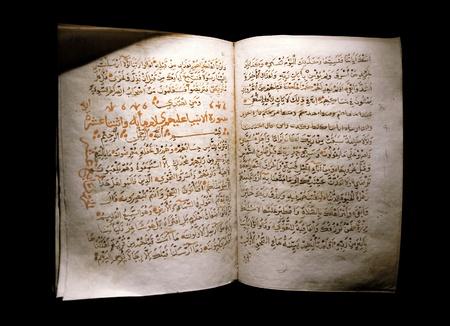 Koran open on a black background photo