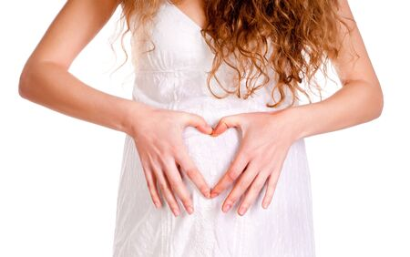 Woman holding her hands in a heart shape on her pregnant belly photo