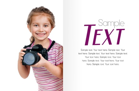 cute little girl with a camera looking for a white blank with sample text photo