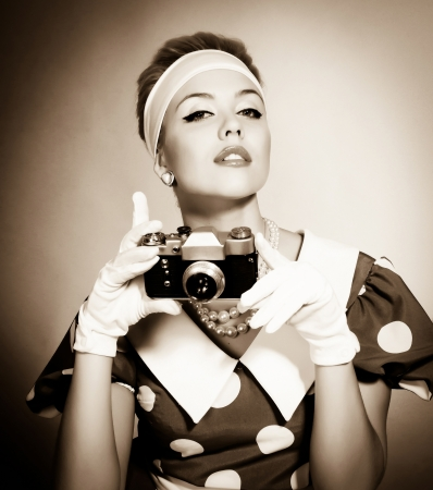 taking photograph: beautiful young lady with a camera in retro style Stock Photo