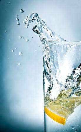 vaso con agua: rodaja de limón gotas en un vaso de agua