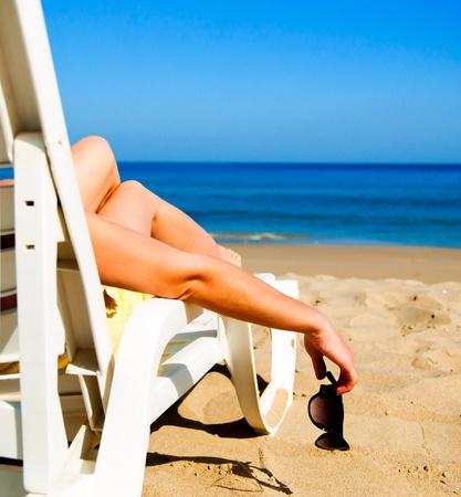 nue plage: fille allongé sur un transat de plage avec des lunettes à la main
