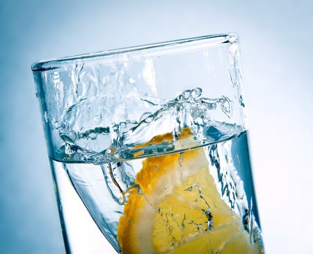 slice of lemon drops in a glass of water photo