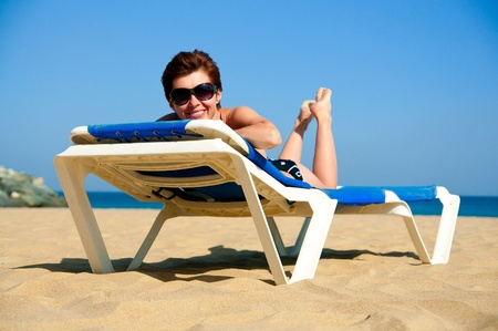 beautiful girl relaxes on a lounger in sunglasses photo