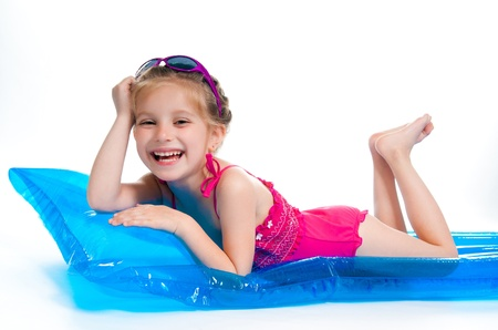 kids swimming pool: cute little girl in a swimming suit on an inflatable mattress