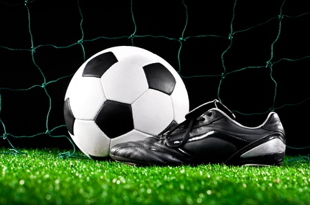 soccer ball and cleats on the football field Stock Photo - 13820248