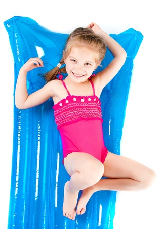 child in bikini: cute little girl in a swimming suit on an inflatable mattress