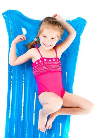 enfant maillot de bain: jolie petite fille dans un maillot de bain sur un matelas gonflable