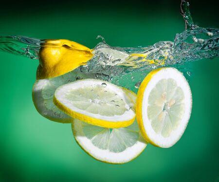 splashing lemon into fresh water photo
