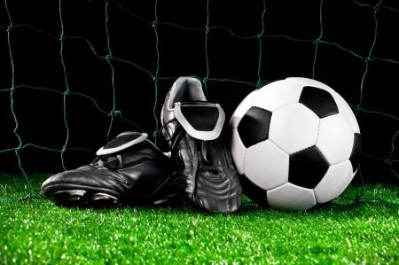 futbol: pallone da calcio e tacchetti sul campo di calcio Archivio Fotografico