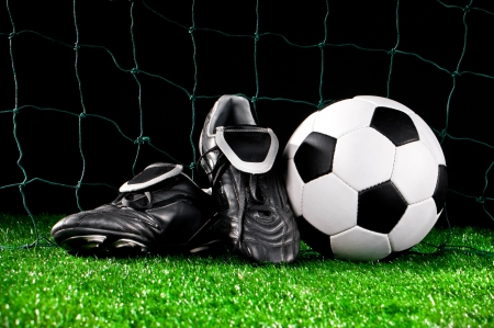 futbol: soccer ball and cleats on the football field Stock Photo