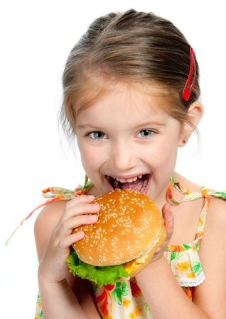 Pretty little girl eating a sandwich isolated on white background photo