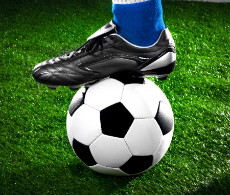 football boots: soccer payer withl with his foot on the football field Stock Photo