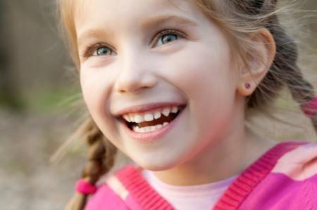 jolie petite fille: jolie petite fille souriante dans un parc close-up