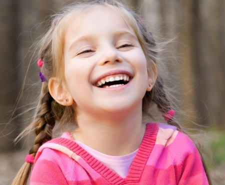 face of infant: cute little girl smiling in a park close-up