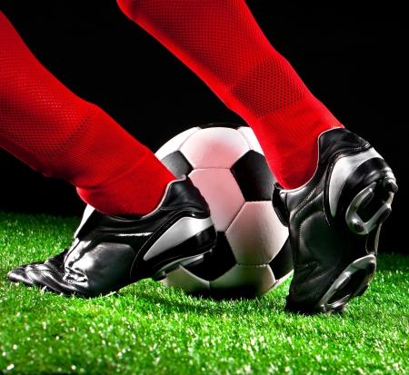 joueurs de foot: ballon de soccer et les pieds sur le terrain de football