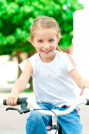 niños en bicicleta: hermosa niña en una bicicleta en el parque Foto de archivo