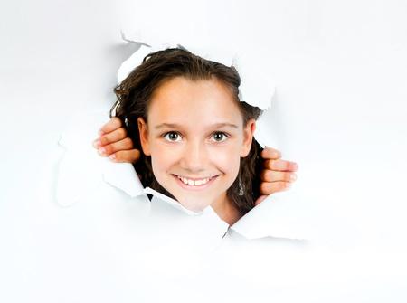 niños con pancarta: Hermosa niña mira hacia fuera de una hoja de papel rasgado