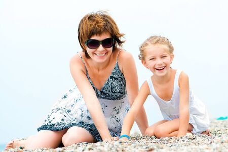 mother with daughter play on a beach Stock Photo