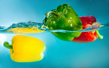colorful peppers splashing into blue water photo