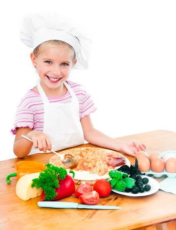 Young girl preparing a pizza on a white background photo
