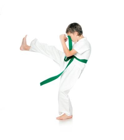 Boy in kimono with green belt practising  on a white background photo