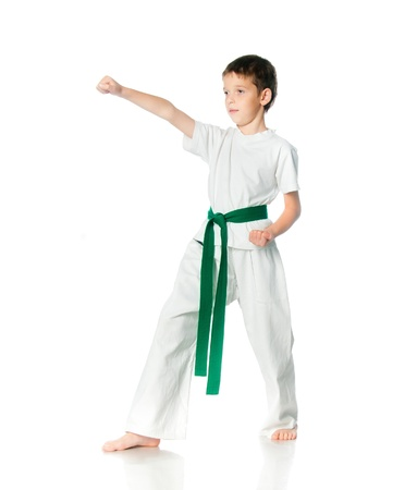 karate boy: Young boy in kimono with green belt practising  on a white background
