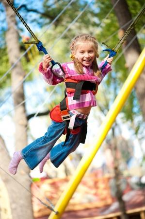 bungee jumping: Ni�a saltando en la cama el�stica con bandas de goma